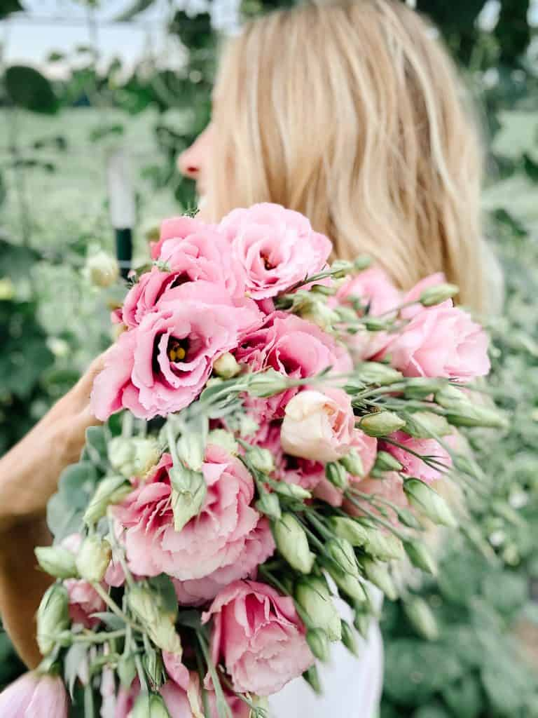 Young woman with blonde hair in a garden with a large bunch of freshly cut pink flowers thrown over her shoulder.