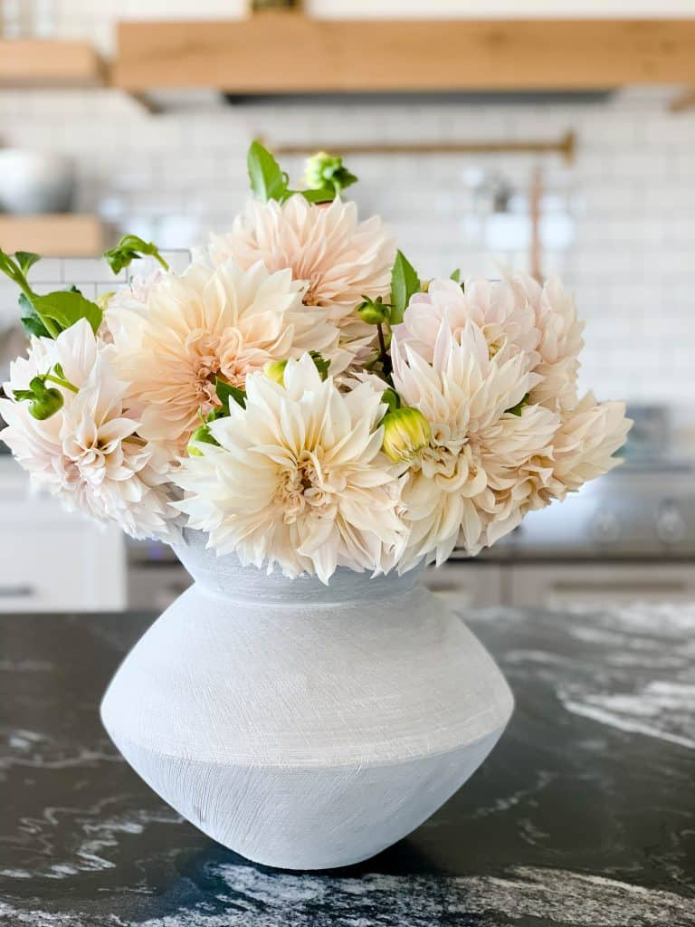 A large and beautiful bouquet of peach and cream colored dahlias arrangement in a cement gray sculptural vase set atop a dark black granite kitchen island.