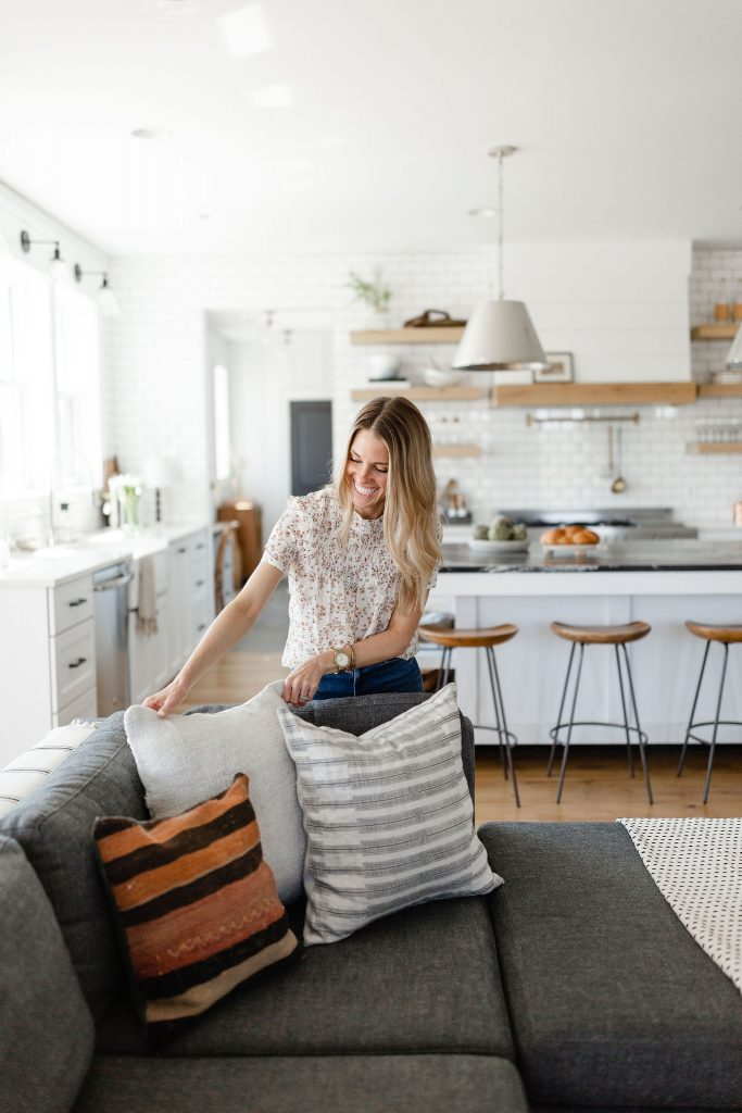 Interior designer arranging pillows on a charcoal gray sofa in a light and bright open concept modern farmhouse with a white kitchen clad with subway tile in the background.